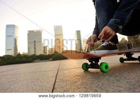 closeup of skateboarder hands tying shoelace at sunrise city