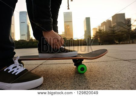 closeup of skateboarder tying shoelace at sunrise city