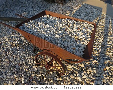 Vintage rusty wheelbarrow loaded with stone in a nostalgic tool display in Wisconsin