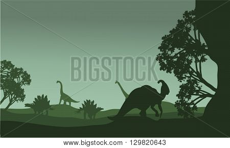 Silhouettte of parasaurolophus and stegosaurus in the fields