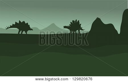 stegosaurus in fields scenery silhouette with green backgrounds