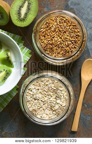 Toasted oat grains and oat flakes in jars with yogurt and kiwi on the side photographed overhead on slate with natural light (Selective Focus Focus on the top of the oats)