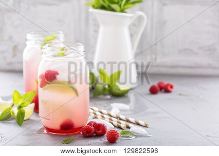 Cold green iced tea in mason jars with lime and raspberry