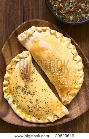 Chilean Empanadas baked stuffed pastry photographed overhead on dark wood with natural light. The empanada with the oregano on top is stuffed with ham cheese tomato and oregano the one with the sesame is stuffed with ham and cheese.