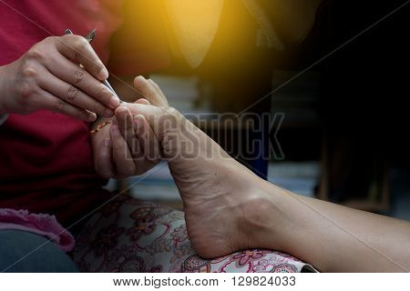 professional doing manicure pedicure work on hand and foot