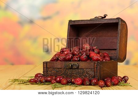 Rose hips in a wooden chest on a background of autumn leaves.