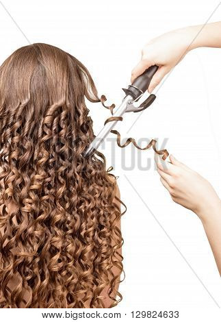 Hairdresser makes using forceps curly hair woman isolated on white background.
