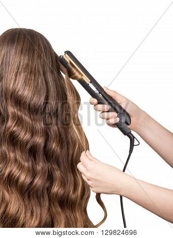 Hairdresser makes curly long brown hair isolated on white background.