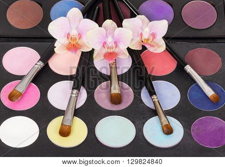 Eyeshadow palette, makeup brushes and orchid flowers on a black background.