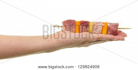 Female hand holding a skewer with slices of raw meat and vegetables isolated on white background.