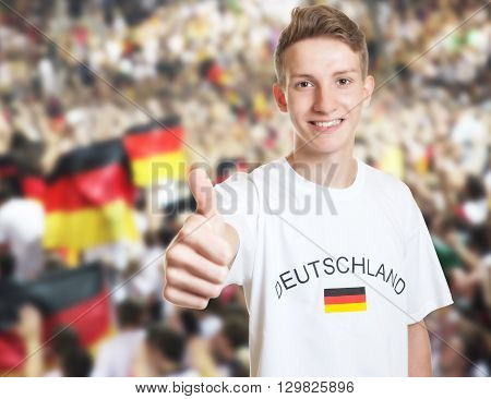 Handsome german fan showing thumb with other fans in the background