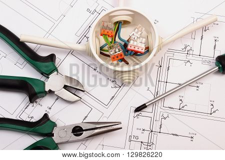 Metal pliers screwdriver and cable connections in electrical box lying on electrical construction drawing of house work tool and drawing for engineer jobs