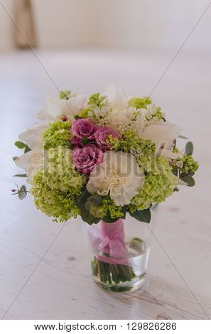 Vase with small bouqet of spring green and purple flowers