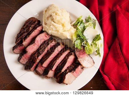 sliced rare beef rib eye steak with caesar salad and mashed potato