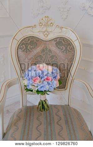 A white antique chair with a blue flower bouqet lying on it