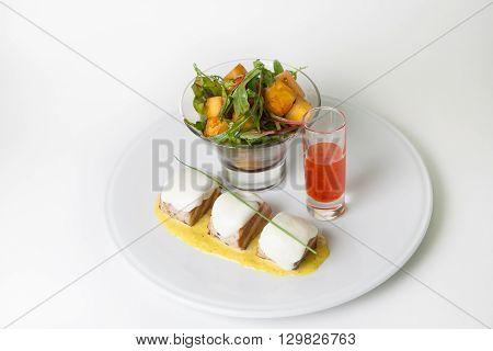 Tenderloin fried steaks with arugula garnish and chili sauce