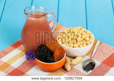 Healthy breakfast. Pitcher juice, dried fruit and corn balls on blue frne.