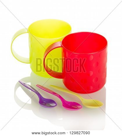 Bright plastic cups and spoons isolated on white background.