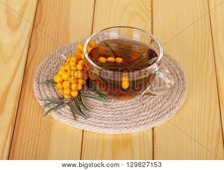 Bunch of sea buckthorn and cup of tea on a background of light wood.