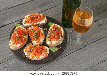 Sandwich with tomatoes goat cheese and basil on a wooden table with a glass of white wine. Tasty appetizer wine