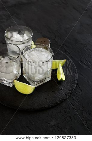 Cocktail vodka or gin with ice and lime on a dark background