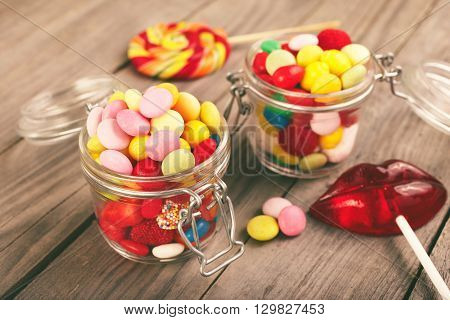 Two glass jars of colorful candy on a wooden table closeup