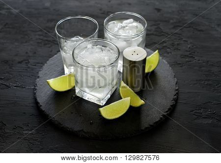 Vodka or gin with ice and lime on a dark background closeup