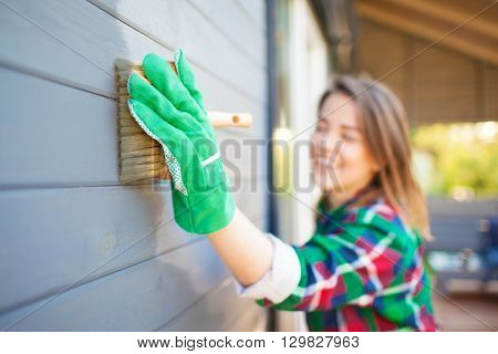 Cheerful young woman applying protective varnish or paint on wooden house tongue and groove cladding elevation wall. Focus on hand with brush. House improvement  diy concept.
