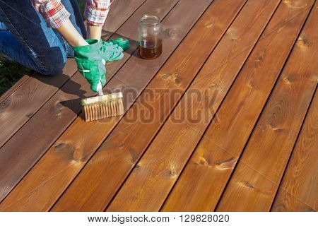 Woman applying protective varnish or wood oil on a patio wooden floor, house maintenance concept