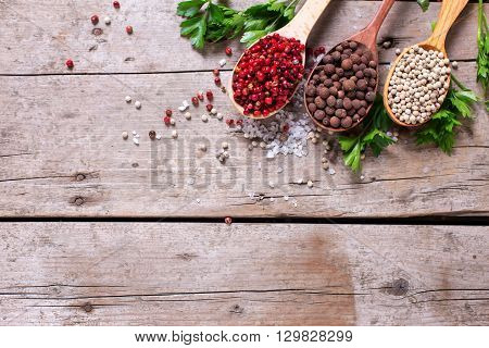 Seasoning for cooking. Red white and allspice pepper in wooden spoons on aged wooden background. Food ingredient. Selective focus. Flat lay. Top view. Place for text.