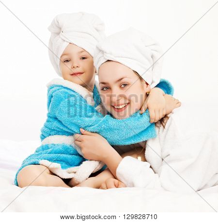 mother and daughter wearing bathrobes in bed at home