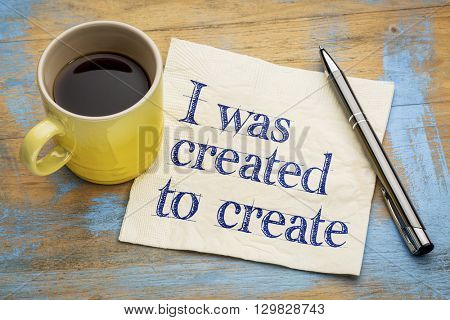 I was created to create positive affirmation note - - handwriting on a napkin with a cup of espresso coffee