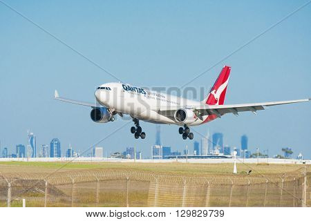 Melbourne, Australia - May 6, 2016: Close-up view of a Qantas passenger airplane landing at Melbourne Airport, with CBD skyline in the background