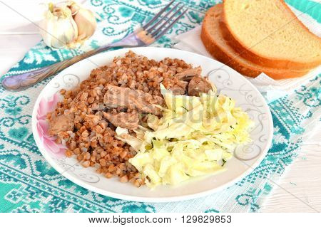 Buckwheat porridge with meat, cabbage salad, bread, garlic, fork on a green napkin. Simple recipe for every day