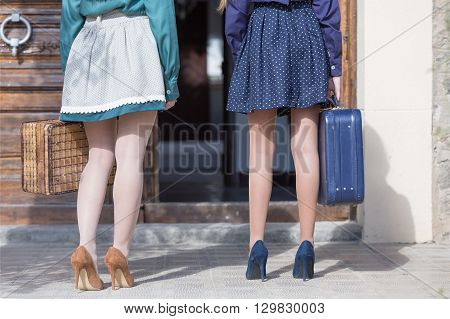 Back view of two young women on heels holding suitcases while standing outdoor in sunlight