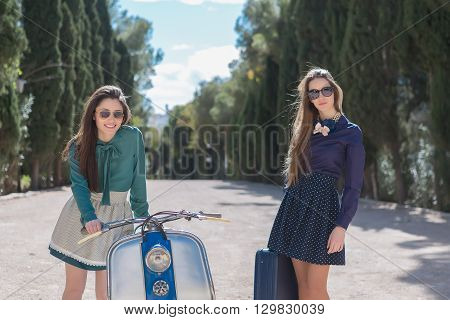Two elegant women standing near motorbike with suitcase.