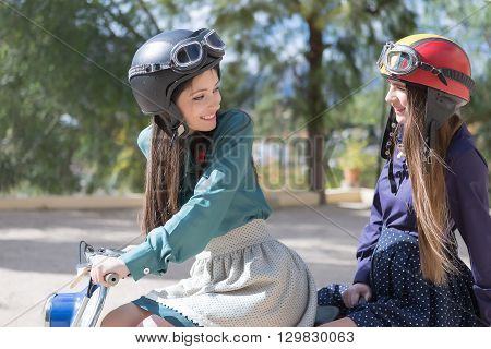Two girlfriends in helmets riding a retro bike smiling