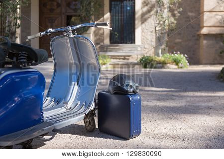 Steel retro motorcycle parked against of house with blue suitcase and helmet
