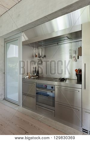 Domestic stainless steel kitchen, hob with objects
