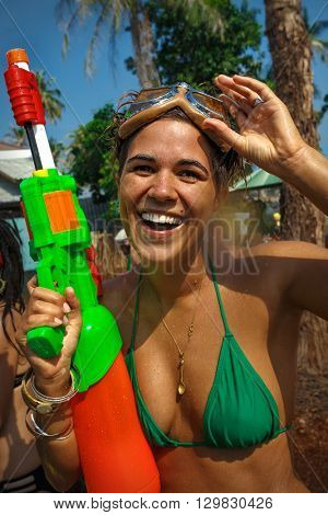 Young woman with water gun has a fun