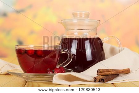 Pitcher and drink a cup of rose hips, vanilla sticks on a background of light wood.
