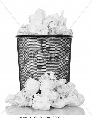 Metal trash can overflowing with paper waste isolated on white background.