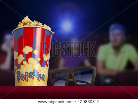 3d glasses and popcorn on red armchair cinema