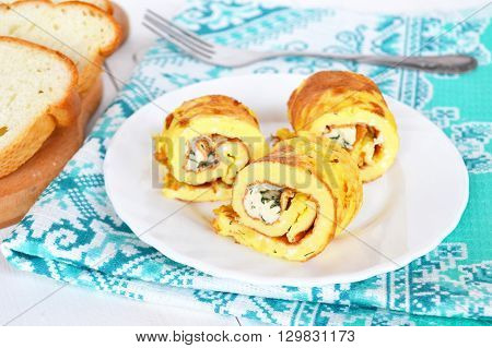 Omelette with cheese on a plate, bread, fork