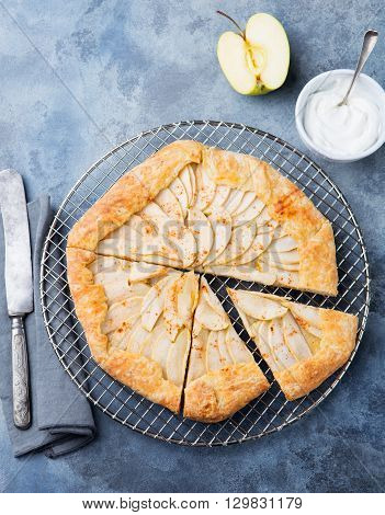 Apple galette, pie, tart with cinnamon on cooling rack on a blue stone background. Top view