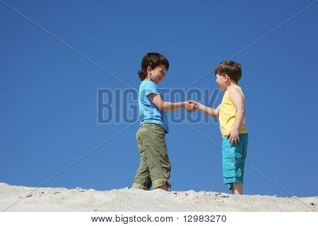 Two boys greet on sand