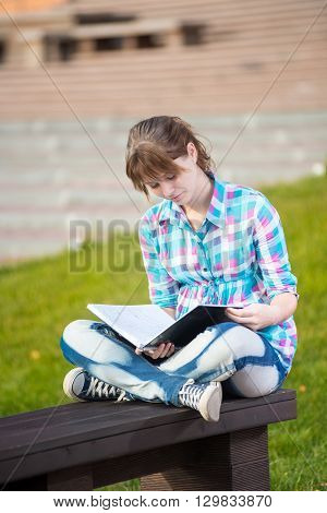 Student girl with copybook on bench outdoor. Summer campus park. Studying to exam.