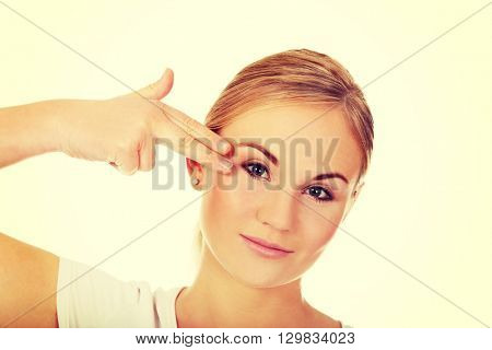 Young woman committing suicide with finger gun gesture