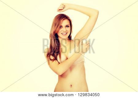 Beautiful young woman using antiperspirant