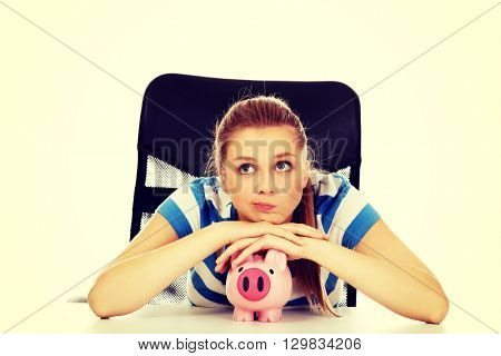 Teenage woman with piggybank on the table